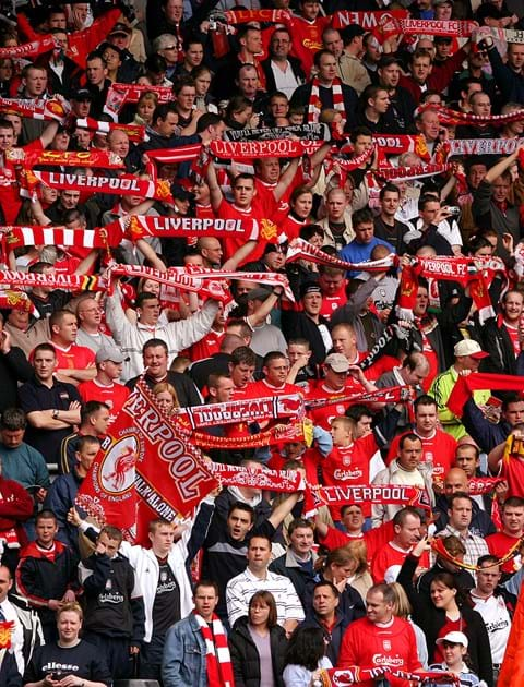 Fans of liverpool fc in football stadium in red jerseys